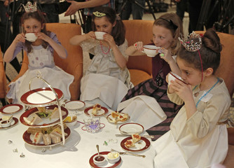 Young girlsdrink tea during a 'Princess Prep' class training afternoon to learn how to be a princess in London
