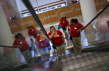 Employees at a new CityTarget store ride the escalator as they prepare for its opening in downtown Chicago