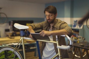 Employee using digital tablet by vintage bicycle at workshop