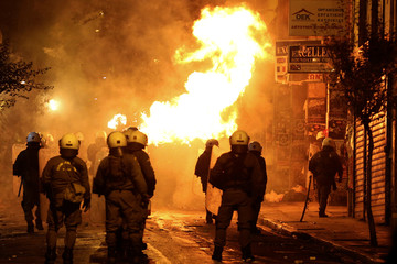 A petrol bomb explodes next to riot police during clashes following an anniversary rally marking the 2008 police shooting of 15-year-old student, Alexandros Grigoropoulos, in Athens