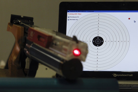 A laser gun is seen next to a target displayed on a laptop during a training session at the shooting range in Montelibretti
