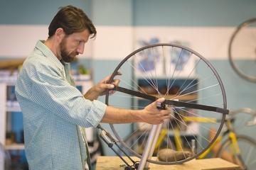 Side view of focused worker repairing wheel at workshop