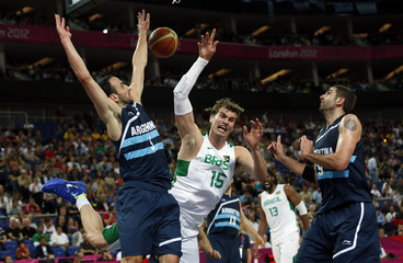 Brazil's Splitter collides with Argentina's Ginobili and Gutierrez during their men's quarterfinal basketball match at the North Greenwich Arena in London during the London 2012 Olympic Games