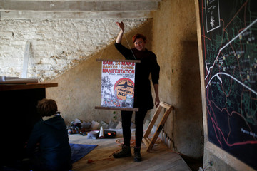 """A resident poses inside the information point at """"La Rolandiere"""" area in the zoned ZAD (Deferred Development Zone) in Notre-Dame-des-Landes"""