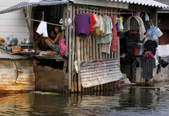 Residents sit in a house at a flooded area in Bangkok