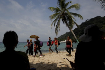 Tourists look at Cuban migrants arriving to the beach safely after crossing the border from Colombia through the jungle into La Miel, in the province of Guna Yala, Panama