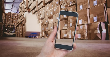 Hand photographing boxes in warehouse