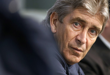 Manchester City's manager Pellegrini listens to a question during a news conference in Manchester