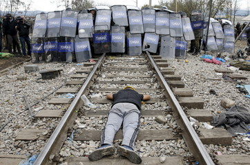 A stranded migrant lays on the rail tracks in front of a Macedonian police cordon as they clash after a migrant was electrocuted and badly burned when he climbed on top of a train wagon, near the village of Idomeni