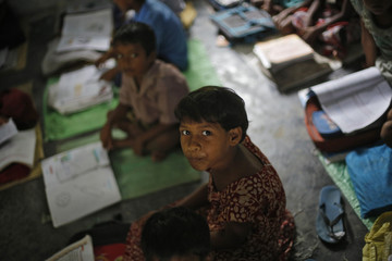 A school girl watches the camera while studying inside her classroom before having the free mid-day meal in Chapra district