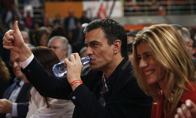 Socialist party leader Sanchez drinks water as he gestures next to his wife Gomez before the final campaign rally for Spain's general election in Fuenlabrada