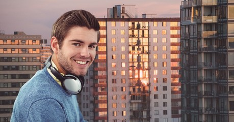 Smiling hipster with headphones against buildings