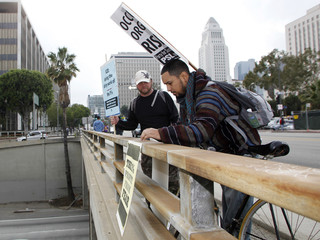David Paz of Compton, California hangs a sign on a freeway overpass with Los Angeles City Hall seen in the background as Tim Trepanier looks on during an Occupy ICE protest march in Los Angeles