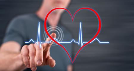 Man touching a heart beats graph on a touch screen