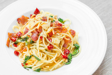 Spaghetti with fried crispy bacon and chili fried basil leave hot and spicy food delicious international cuisine in Thailand style