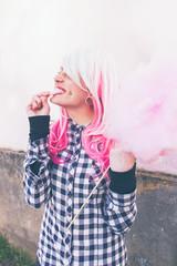 Adolescente alternativa con piercings y el pelo teñido comiendo algodón de azúcar