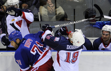 HC Slovan Bratislava's Michal Dobron collides with New York Rangers' Mike Rupp during their pre-season NHL hockey game in Bratislava