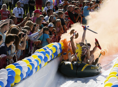 Participants slide down on a chute on a float to cross a 26-metre long pool of water and foam during a competition at the Bobrovy Log Ski Resort near the Siberian city of Krasnoyarsk