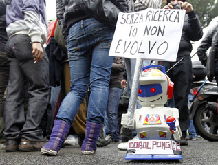 A small toy robot holds up a sign during a demonstration in Rome