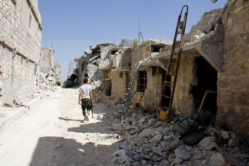 A Free Syrian Army fighter walks through a damaged street in Aleppo's Sheikh Saeed neighbourhood