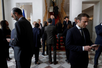 French President Emmanuel Macron and Prime Minister Edouard Philippe use their smartphones after a family photo after the first cabinet meeting at the Elysee Palace in Paris