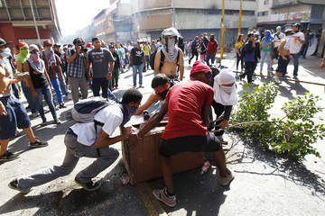 Opposition demonstrators block a street during a protest against Venezuela's President Maduro's government in Caracas