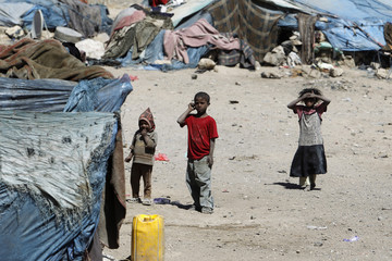 Children stand outside their huts in a slum area in Raida town, some 60km (37 miles) northwest of the Yemeni capital Sanaa