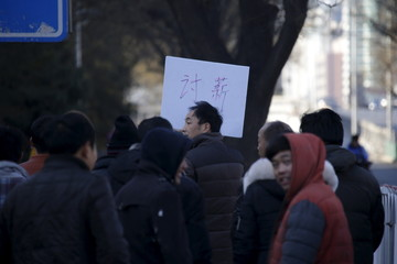 Tian Honglei (C), a migrant worker from Henan province, holds a placard as he marches with his fellow workers along a main street to protest against a construction site and demand their salaries, in central Beijing