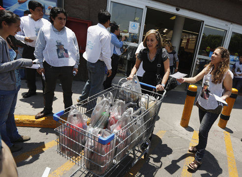 Labor rights activists distribute flyers to customers during a protest at a Walmart store in Mexico City