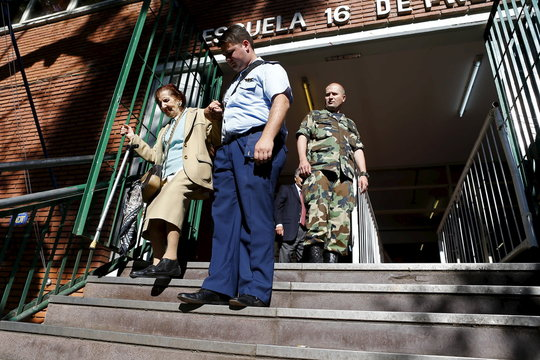 A police officer helps a woman go down the stairs after she voted in the presidential election at Buenos Aires