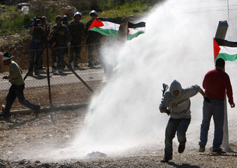 A Palestinian protester runs from a water cannon during clashes at a protest in Bilin near Ramallah