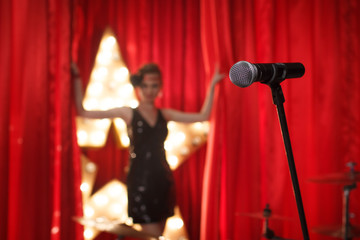 Microphone on theater stage ,golden star on background with with woman,opening red curtains