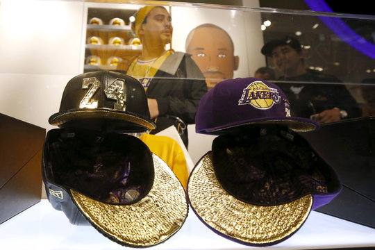 Fans look at a Kobe Bryant 18k gold and leather baseball cap and a purple diamond cashmere baseball cap in the Lakers store at Staples Center on the last day of Kobe's 20-year career with the team, in Los Angeles