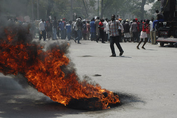 Residents burn two tyres as they take part in a protest near the destroyed national palace during the visit of former U.S. presidents Bush and Clinton in Port-au-Prince