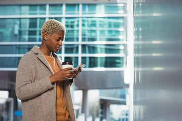 Female executive using mobile phone while having coffee