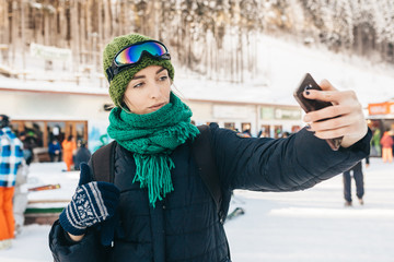 """The beautiful girl takes a selfie on the street. On her a green cap, a menthol scarf, a blue jacket and ski points. She shows """"class""""."""