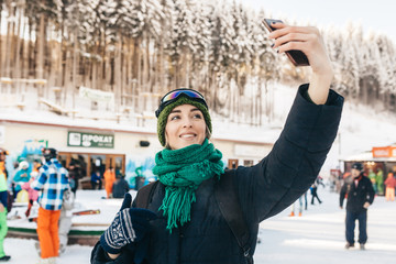 The attractive girl in a blue jacket, a green cap and a menthol scarf takes a selfie. Also on her ski points. The girl perfectly smiles.