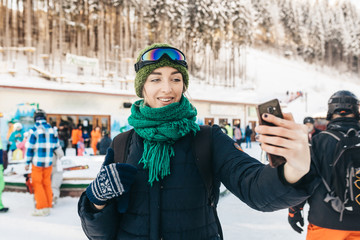 The beautiful girl takes a selfie on the street. She is warmly dressed, on her a menthol scarf, a green cap and a blue jacket. Still the girl has at herself ski points.