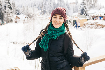 The beautiful girl walks in winter day. On her a menthol scarf, a lilac cap and a blue jacket. She holds the braid and lovely smiles.