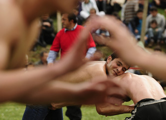 Wrestlers covered in oil take part in a traditional oil wrestling competition in the village of Studenicani near capital Skopje