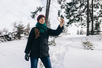The pretty girl takes a selfie against the background of a landscape. On the street winter. On the girl a warm blue jacket, a lilac cap and a menthol scarf.