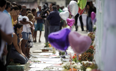 Woman reacts next to balloons, flowers, and notes of condolence placed in front of Tasso da Silveira school where gunman opened fire on children in Rio de Janeiro