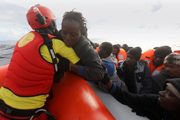 A lifeguard pulls a migrant woman to a rescue craft  from an overcrowded raft, as lifeguards from the Spanish NGO Proactiva Open Arms rescue all 112 on aboard