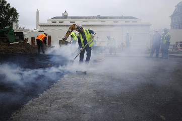 Workers spread asphalt to repave a section of the driveway as substantial utility work continues in front of the West Wing of the White House in Washington