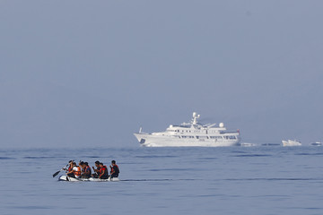 Migrants in a dinghy paddle past a luxury yacht which cruises on Mediterrean Sea as they attempt a crossing to the Greek island of Kos, off the shores of Bodrum