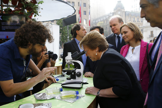 Chile's President Bachelet looks through a microscope during the opening ceremony of the Congress of the Future event in Santiago