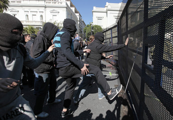 Anti-austerity demonstrators kick police fences blocking a street leading to the parliament in Athens during clashes with riot police