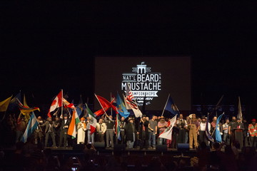 Contestants wave flags to commence the 2015 Just For Men National Beard & Moustache Championships at the Kings Theater in the Brooklyn borough of New York