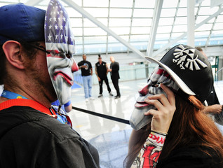 A couple wearing Payday 2 clown masks look at each other while waiting in line during E3 in Los Angeles