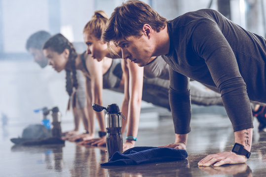 group of athletic young people in sportswear doing push ups or plank at the gym, group fitness concept